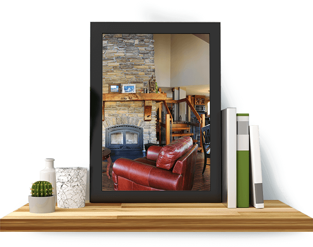 A framed picture of a living room, set atop a shelf